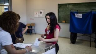 سيدة تدلي بصوتها في الانتخابات العامة في مركز اقتراع بأثينا في 7 يوليو/تموز 2019.