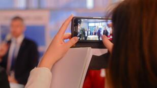 Une journaliste prend en photo Laurent Wauquiez, lors d'une conférence de presse à Lyon, le 9 février.