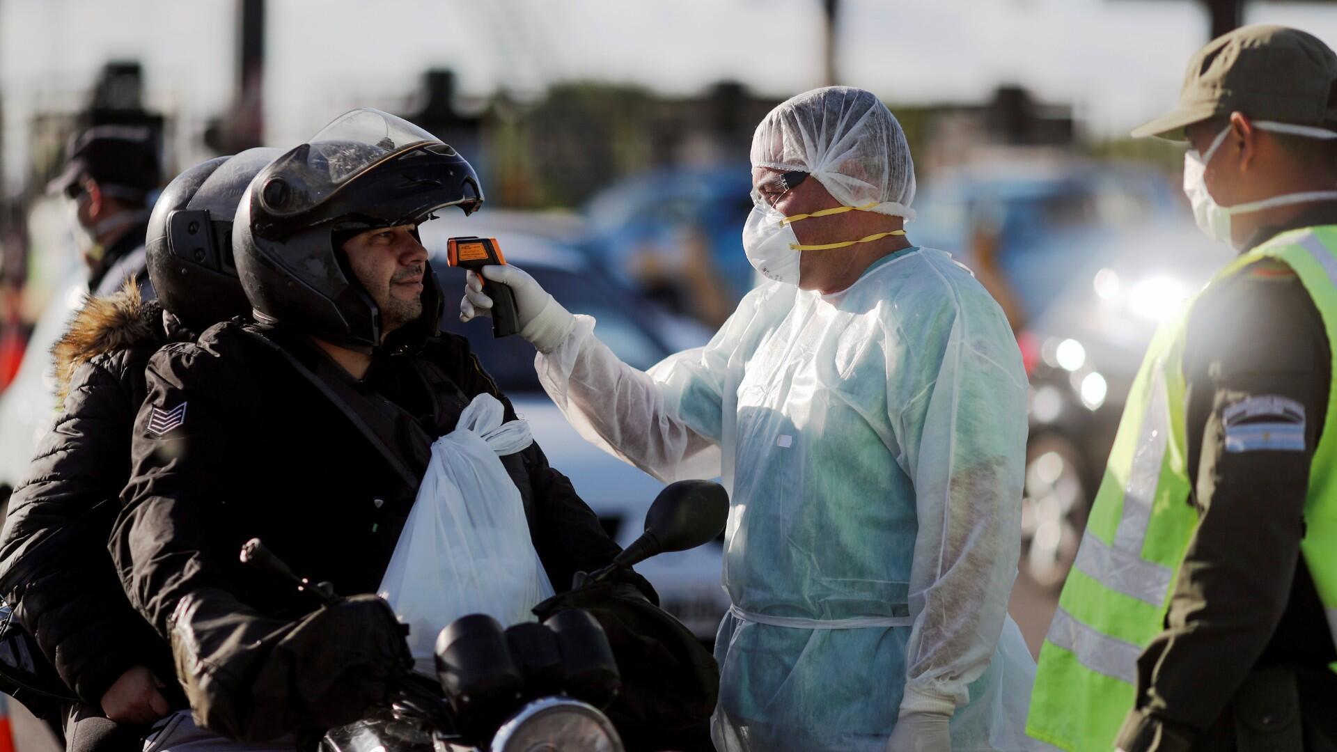 Un trabajador de salud toma la temperatura de un conductor por precaución debido a la enfermedad por coronavirus (COVID-19), en Buenos Aires, Argentina, 19 de marzo de 2020.