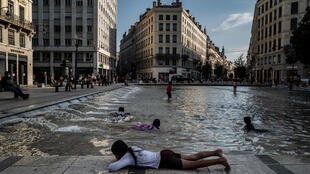Children play in a fountain to cool off in the center of Lyon, France