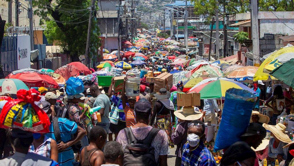 Habitantes de Puerto Príncipe, Haití, se abastecen de alimentos en el mercado callejero de Pétion-Ville, un lugar con aglomeraciones este 25 de abril de 2020 a pesar de que las recomendaciones de distanciamiento social.