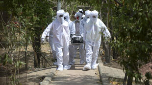 متطوعون ينقلون جثة أحد ضحايا كوفيد-19 لدفنها في شيناي في 16 حزيران/يونيو 2020.