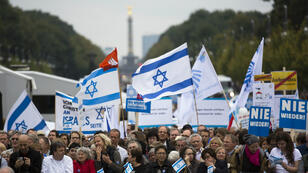 "People with Israeli flags and banners attend a rally against anti-Semitism entitled ""Stand Up! Jew Hatred - Never Again!"" in Berlin on September 14, 2014."
