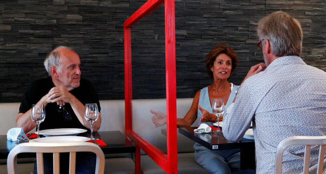 Los administradores de un restaurante prueban una barrera protectora instalada entre las mesas cuando el país comienza a ampliar medidas de desconfinamiento tras el cierre de coronavirus. Bruselas, Bélgica, el 2 de junio de 2020.
