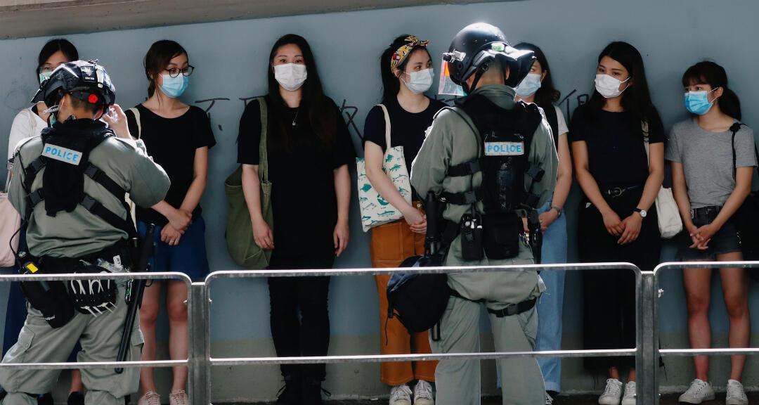 La Policía antidisturbios se detiene y busca personas durante una marcha en el aniversario del traspaso de Hong Kong a China. Hong Kong, 1 de julio de 2020.
