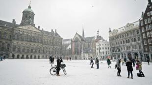 Peatones en la plaza del Dam de Ámsterdam cubierta de nieve, el 7 de febrero de 2021