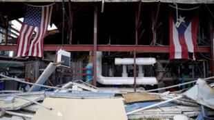 Las banderas de Estados Unidos y Puerto Rico cuelgan en el interior de una iglesia destruída por el huracán María en la isla caribeña.
