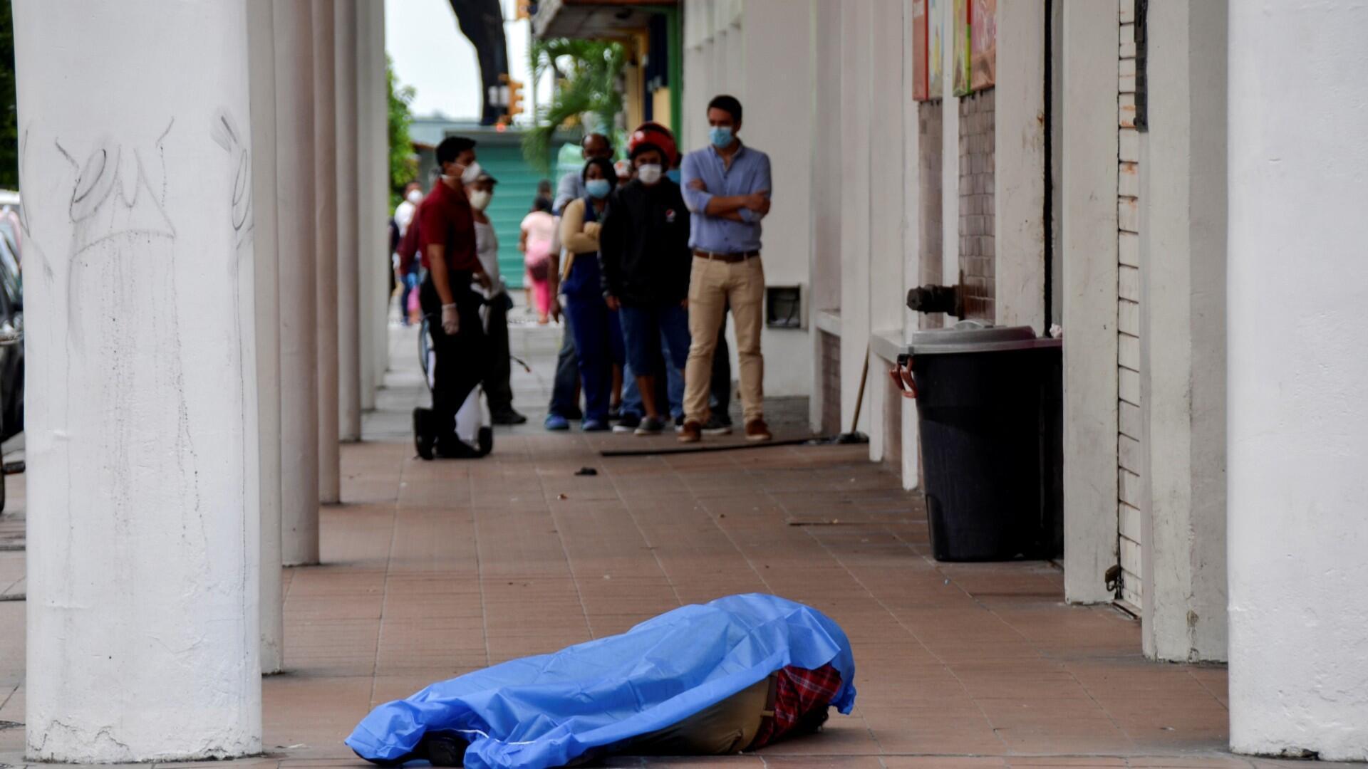 La gente hace cola afuera de una tienda cerca del cadáver de un hombre que se había derrumbado en la acera, durante el brote de la enfermedad por coronavirus (COVID-19), en Guayaquil, Ecuador, 30 de marzo de 2020.
