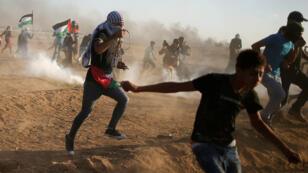Los palestinos huyen del gas lacrimógeno disparado por las tropas israelíes durante una protesta en la zona fronteriza entre Israel y Gaza, el 14 de septiembre de 2018.