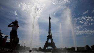 Una mujer disfruta un día de verano en la fuente de Trocadero al frente de la Torre Eiffel en París. Agosto 4, de 2019