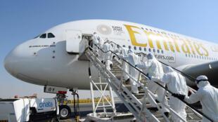 """عمال نظاقة يدخلون طائرة تابعة لمجموعة """"طيران الإمارات"""" لتعقيمها في مطار دبي في 8 آذار/مارس 2020"""