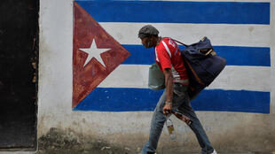 A man walks next to a mural of the Cuban flag in Havana in January 2021
