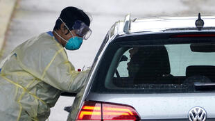 A US healthcare worker takes a swab from a patient at a drive-through site in Arlington, Virginia, on March 19, 2020.