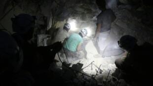 """مسعفون من """"الخوذ البيضاء"""" يبحثون عن ناجين تحت ركام أحد المباني المنهارة في حلب"""