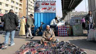 Un vendedor de zapatos espera clientes cerca de un cartel de campaña del presidente de Egipto, Abdel Fatah al Sisi, en El Cairo, el 20 de febrero de 2018.