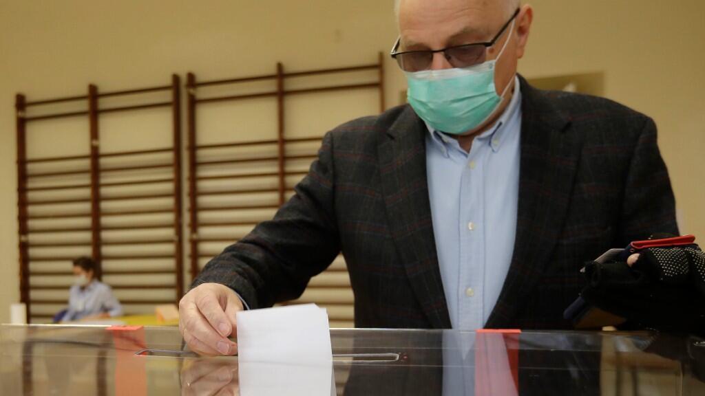 Un adulto mayor polaco se dispone a echar su papeleta a la urna de voto durante las elecciones presidenciales de 2020. En Cracovia, Polonia, el 12 de julio de 2020.