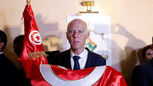 Kaïs Saïed embrasse le drapeau tunisien après l'annonce des sondages de sortie des urnes pour la présidentielle le donnant vainqueur, à Tunis le 13octobre2019.