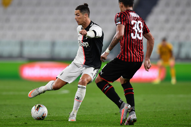 El astro portugués de la Juventus Cristiano Ronaldo (I) intenta escapar del volante brasileño del AC Milan Paqueta, en partido semifinal de la Copa Italia, el 12 de junio de 2020 en Turín