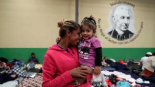 Una migrante hondureña, parte de la caravana que intenta llegar a los EE. UU., lleva a su hija a un refugio para migrantes en Ciudad de Guatemala, Guatemala, el 17 de octubre de 2018.