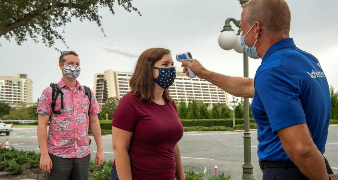 Un trabajador toma la temperatura a una visitante en la entrada de una atracción en el Walt Disney World Resort en Lake Buena Vista, Florida, Estados Unidos.