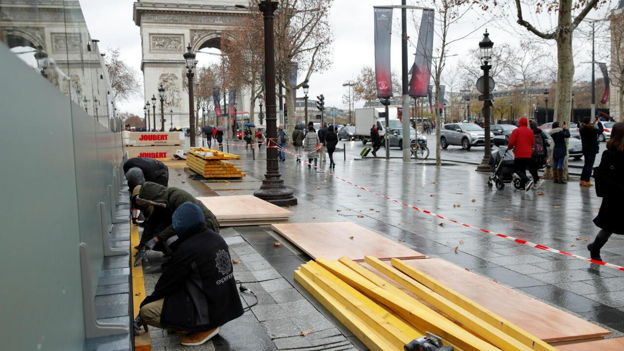 En haut de l'avenue des Champs-Élysées, des commerces installaient des panneaux de protection en bois dès vendredi 7 décembre.