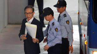 Imagen de archivo. El expresidente surcoreano, Lee Myung-bak (izquierda), es escoltado por las autoridades a una sala de un tribunal, en Seúl, Corea del Sur, el 23 de mayo de 2018.