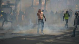 Un manifestant fait face aux forces de l'ordre, dans la fumée des gaz lacrymogènes, à Toulouse le 13 avril 2019.