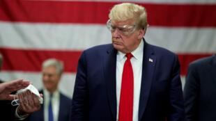 El presidente de Estados Unidos, Donald Trump, observa una mascarilla durante un recorrido por las instalaciones de Honeywell, en donde se fabrican mascarillas para el brote de coronavirus en Phoenix, Arizona, EE. UU. el 5 de mayo de 2020.