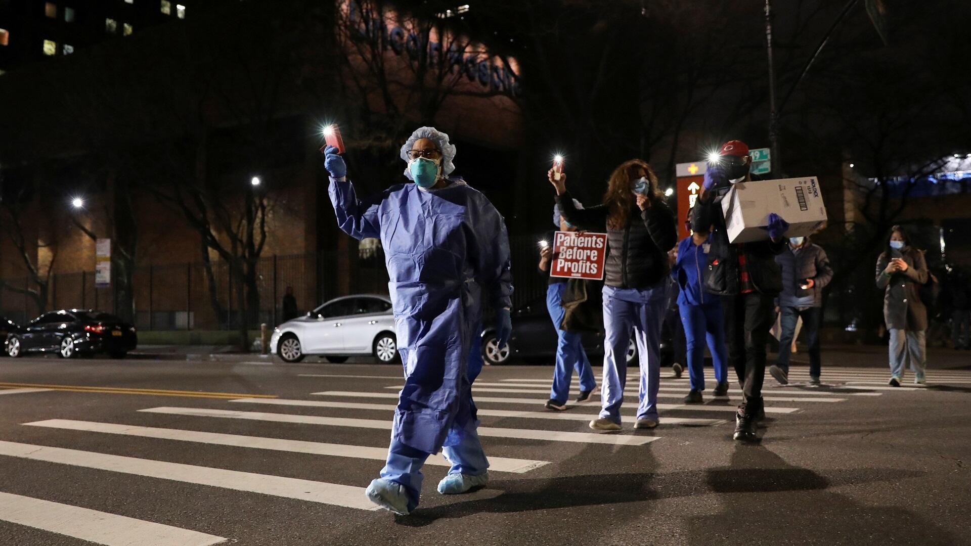 ممرضات وممرضون يتوجهون إلى تجمع لإضاءة الشموع بنيويورك تكريما للعاملين في القطاع الصحي خلال انتشار فيروس كورونا، 14 أبريل/نيسان 2020.
