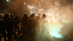 Lebanese security forces react to fireworks hurled toward them by protesters in Beirut, Jan.18, 2020.