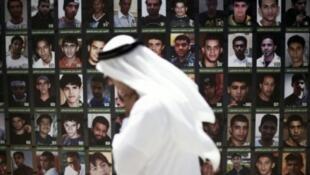 - بحريني يمر أمام صور أشخاص يعتقد أنه تم توقيفهم بعد المشاركة في مظاهرات ضد الحكومة