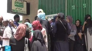 سودانيون ينتظرون دورهم أمام صراف آلي