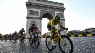 Le peloton, avec le maillot jaune colombien Egan Bernal, descend l'avenue des Champs-Elysées lors de la 21e et dernière étape du Tour de France, le 28 juillet 2019