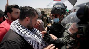 Face à face entre un manifestant palestinien et des membres des forces israéliennes lors d'une manifestation contre le plan israélien d'annexion d'un tiers de la Cisjordanie occupée, près de Tulkarem, le 5 juin 2020.