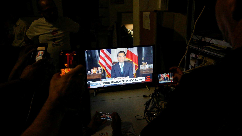 Un grupo de personas observan en la televisión el mensaje de Ricardo Rosselló, quien anunció su renuncia como gobernador de Puerto Rico, en San Juan, el 24 de julio de 2019.