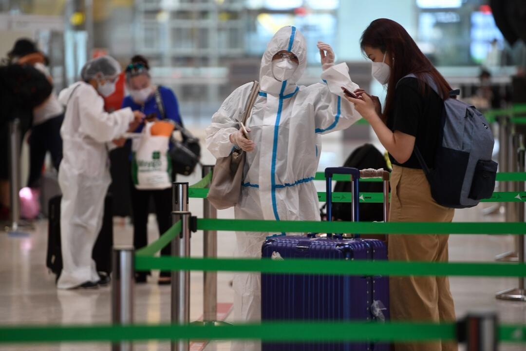 Una pasajera con un traje de protección espera para registrarse para un vuelo con destino a Beijing en el Aeropuerto de Barajas en Madrid, España, el 20 de junio de 2020.