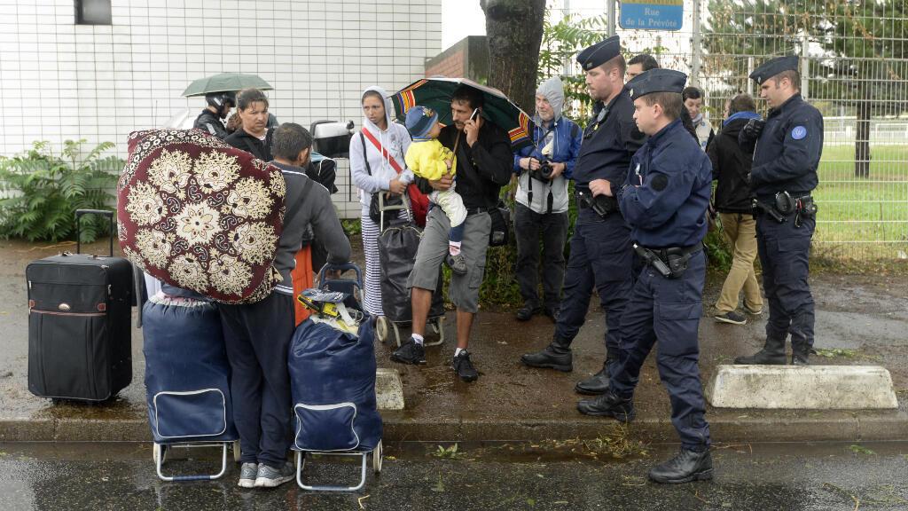 Des policiers se tiennent près d'une famille rom durant l'évacuation forcée du camp de La Courneuve, le 27 août 2015.