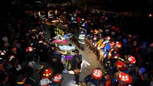 Un grupo de bomberos junto a los cuerpos de las víctimas en el lugar donde se produjo un atropello por un vehículo de transporte pesado en la entrada del municipio de Nahualá, Guatemala, el 28 de marzo de 2019.