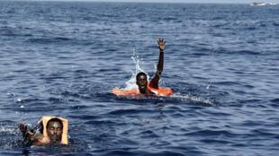 Des migrants appellent à l'aide, au large des côtes libyennes, le 4 octobre 2016.