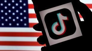 """شعار """"تيك توك"""" على شاشة هاتف آيفون خلفه العلم الأمريكي في آرلينغتون بولاية فرجينيا، في 3 آب/أغسطس 2020."""