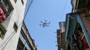 أهالي يراقبون من شرفاتهم طائرة مسيرة تقوم برش مواد مطهرة على شوارع احمد أباد، السبت 9 أيار/مايو 2020
