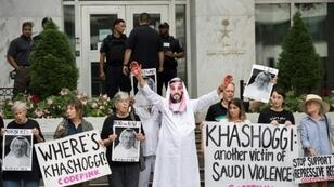 A demonstrator dressed as Saudi Arabian Crown Prince Mohammed bin Salman (C) with blood on his hands protests with others outside the Saudi Embassy in Washington, DC
