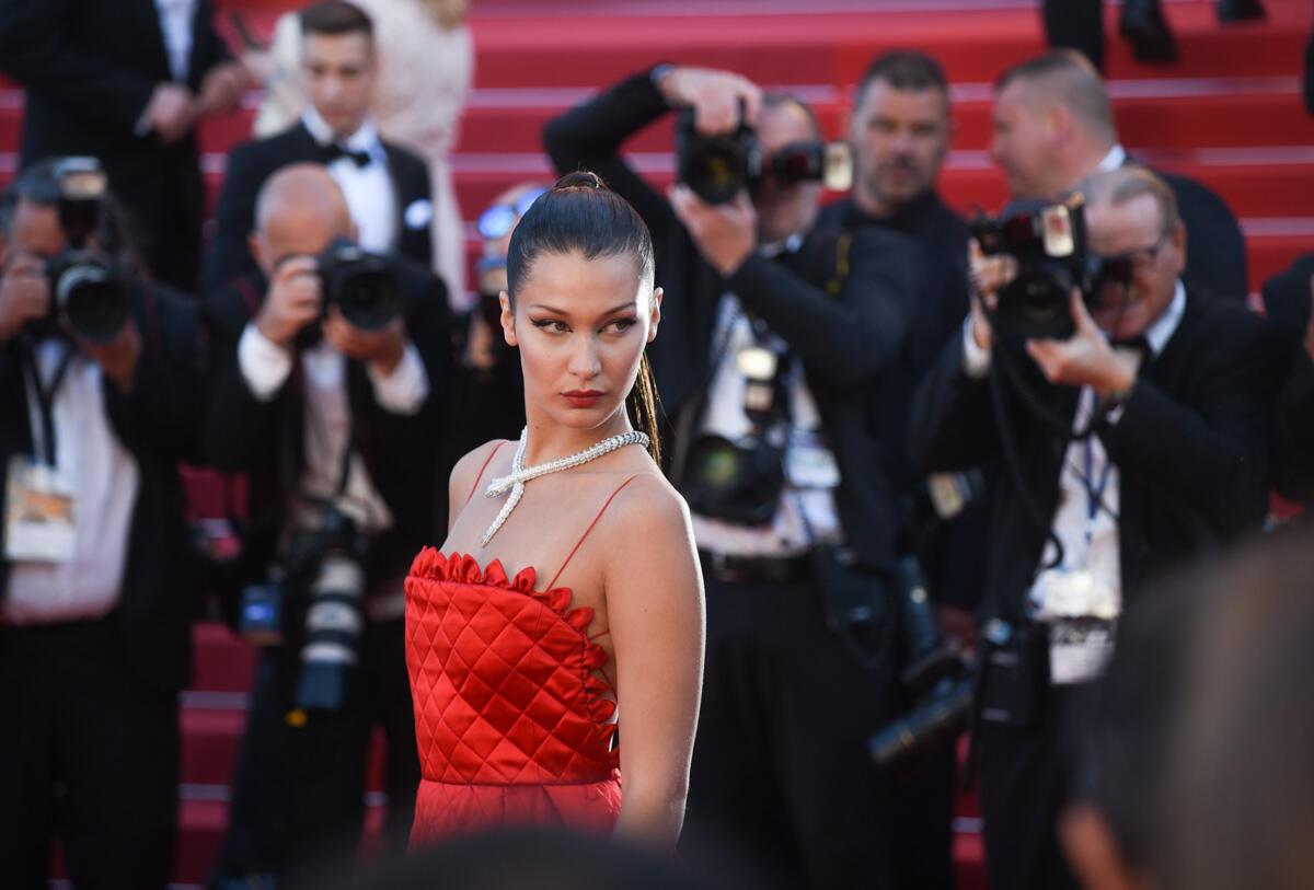 La mannequin américaine Bella Hadid a troqué ses tenues ultra sexy habituelles pour une robe rouge très sage et un collier massif en forme de serpent.