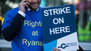 Un pilote de Ryanair tient une pancarte de grève à l'aéroport de Francfort, le 28 septembre 2018.