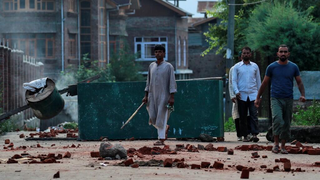 Manifestantes de Cachemira esperan alerta la llegada de los antidisturbios y les esperan con palos y adoquines en el suelo en la ciudad de Srinagar.