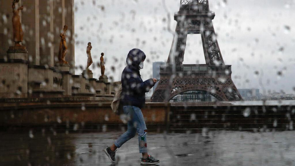 Una mujer con una mascarilla camina el 6 de abril de 2020 por la plaza de Trocadero, frente a la torre Eiffel, en medio del aislamiento obligatorio en el que está toda Francia.