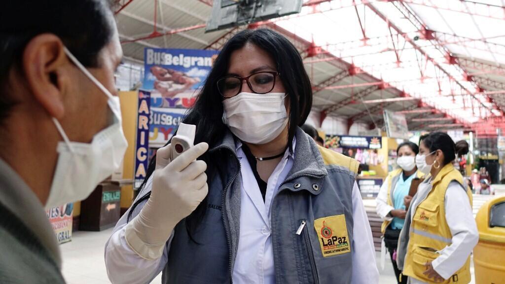 Un trabajador de la salud lee la medición de la temperatura del pasajero durante una rutina de prevención en caso de una emergencia de coronavirus, en la Terminal de Ómnibus de La Paz, Bolivia 4 de marzo de 2020.