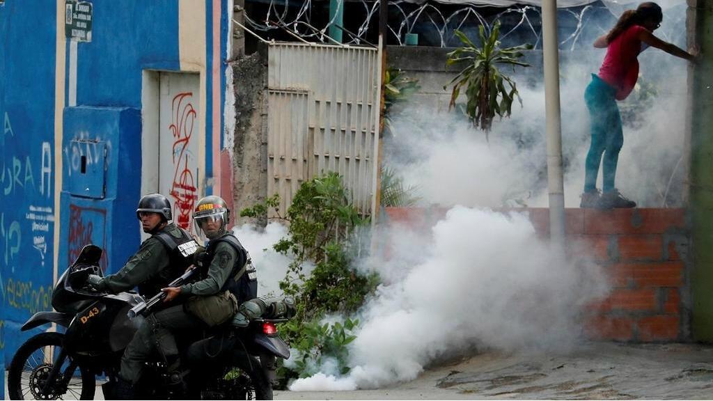Oficiales de la Guardia Nacional aseguran el área cuando una mujer reacciona a un gas lacrimógeno, durante una protesta de simpatizantes de la oposición contra el Gobierno del presidente venezolano Nicolás Maduro en Caracas, Venezuela, el 23 de enero de 2019.