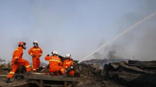 Des pompiers combattent le feu sur le site de l'explosion de Tianjin, le 15 août 2015.