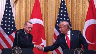 الرئيس الأميركي دونالد ترامب ونظيره التركي رجب طيب اردوغان يتصافحان خلال مؤتمر صحافي في واشنطن العاصمة في 13 تشرين الثاني/أكتوبر 2019.
